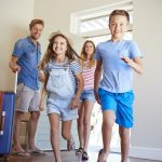 Family Arriving At Summer Vacation Rental