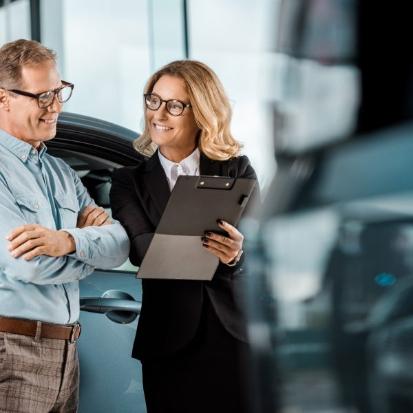 adult man and female car dealer with clipboard standing at showroom