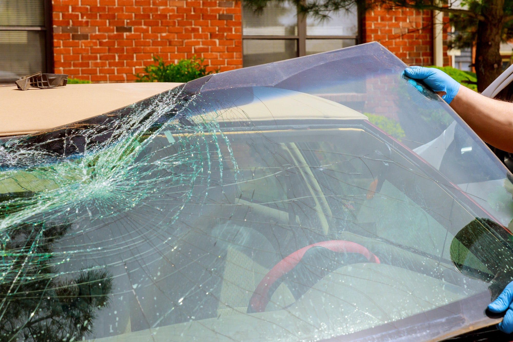 Workers remove crashed windshield of a car in auto oudoors service