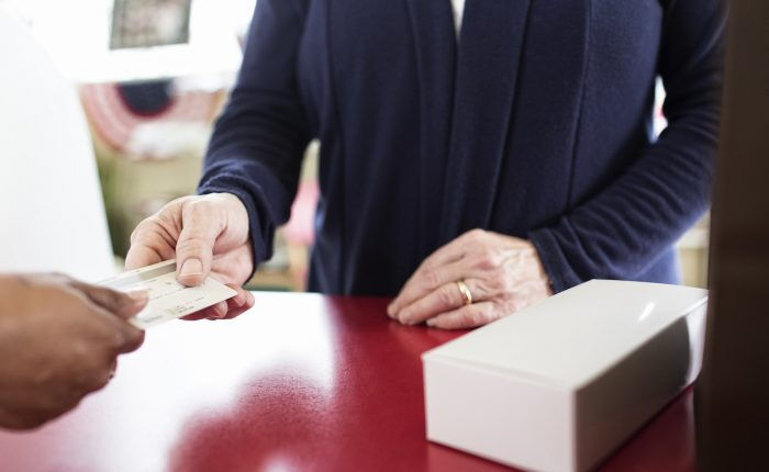 Close up of credit card transaction taking place at a cash register.