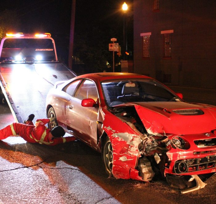 A wrecked car is loaded onto a tow truck after crashing through a brick wall on 17th Ave SW