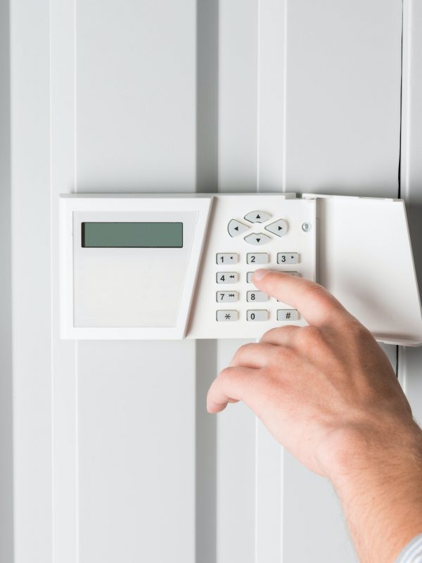 person typing password on home security alarm, security system concept